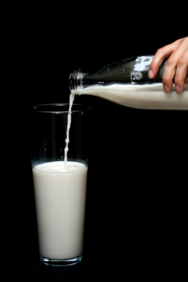 Person pouring calcium into a glass